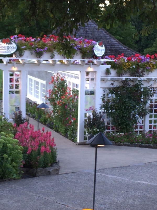 A white structure with blooming plants all around, at Butchart Gardens.