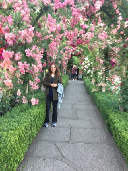 A woman in a rose arbor covered path in bloom, at Butchart Gardens.