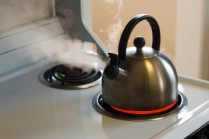 A tea kettle on a stove top.