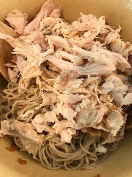 adding chicken to noodles