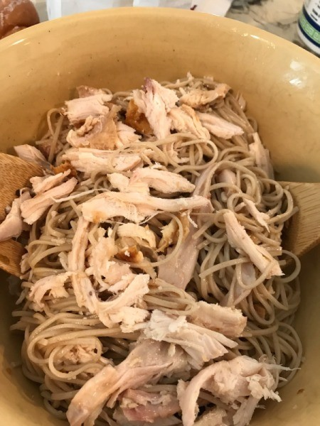 mixing chicken with noodles