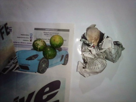 A handful of citrus fruit wrapped in newspaper for storage.