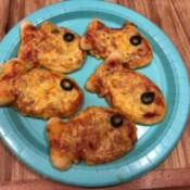 A plate of goldfish shaped cheese pizzas.