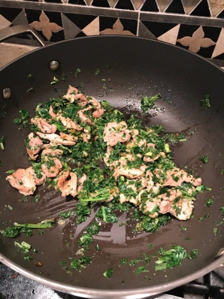 kale/spinach added to pork and onions in wok