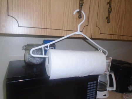 A roll of paper towels on a plastic clothes hanger.