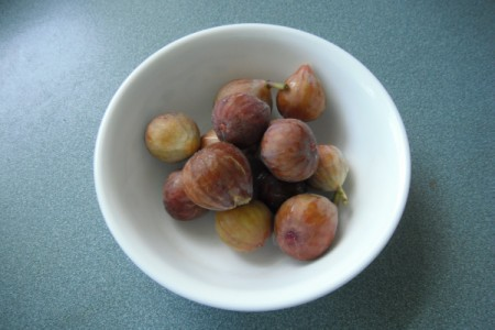 A white bowl containing several figs.