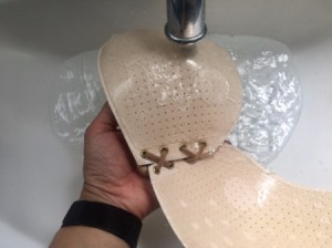 Washing an adhesive bra under a faucet.