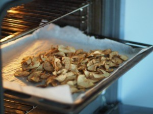 Apple chips being dried in an oven.
