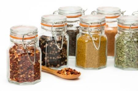 Several glass spice jar full of bulk spices.