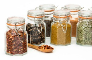Several glass spice jar full of bulk spices.