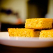 Three pieces of cornbread on a plate.