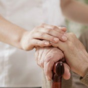 A care attendant standing beside a man at an adult care facility.