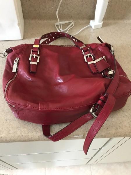 A red Michael Kors handbag found at a thrift store.