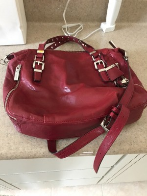 A red Michael Kors handbag found at a thrift store.
