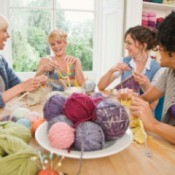A group of friends knitting projects for charity.