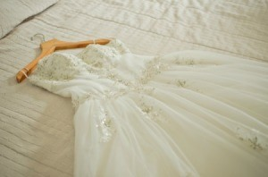 Wedding dress laid out on a bed.