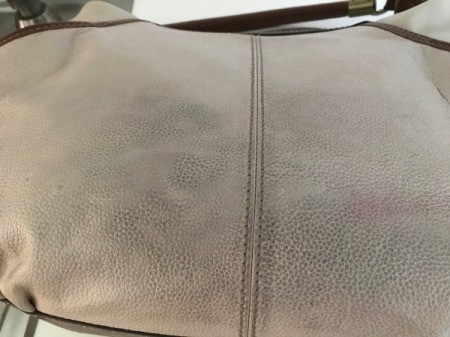 A leather bag that has some discolored marks.