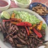 Skillet Carne Asada on plate with peppers lime and cabbage