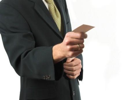 A man holding a business card.