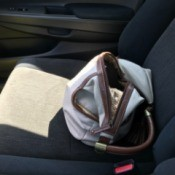A purse being stored in a passenger seat.