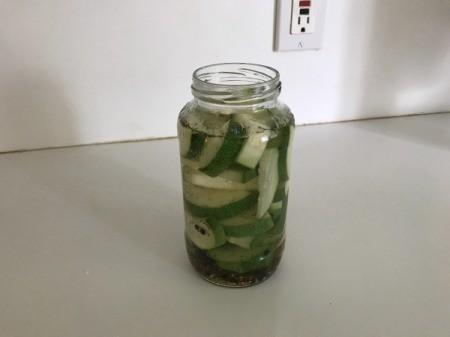 pouring brine over zucchini in jar