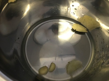 adding lemon juice, garlic and water to pan