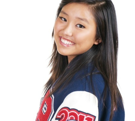 A teen female high school athlete wearing a letterman jacket.