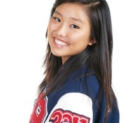 A teen female high school athlete wearing a letterman jacket.