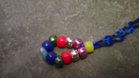 String a bead onto both strands of the ribbon and push down to the other beads.