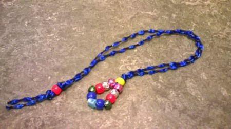 A completed bead and ribbon bookmark, with a blue ribbon and colored beads.