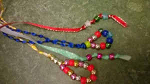 A collection of bead and ribbon bookmarks in different colors.