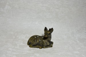 A small fawn figurine on a textured white piece of wallpaper.