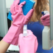 A woman cleaning a mirror with rubber gloves on.