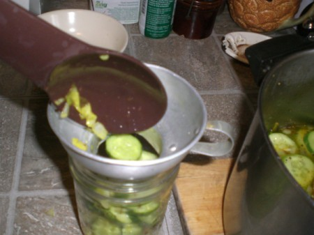filling jar with cut cucumbers