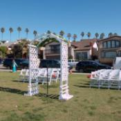 An arbor and white chairs set up outdoors for a wedding.