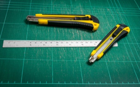 Green cutting mat with a ruler and two cutting tools.