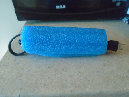 An electrical cord bundled neatly inside a piece of pool noodle.