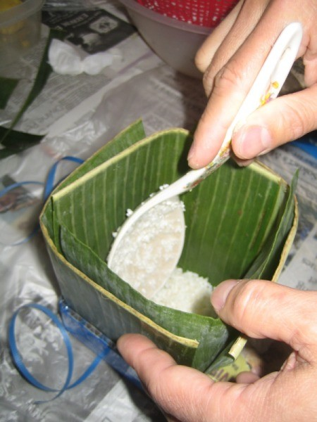 adding rice to banana leaf square