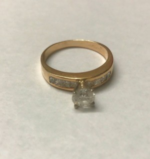 A shiny diamond and gold ring.