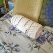 "Crocheted ""Timber"" Neck Pillow Pattern - finished pillow on bed"