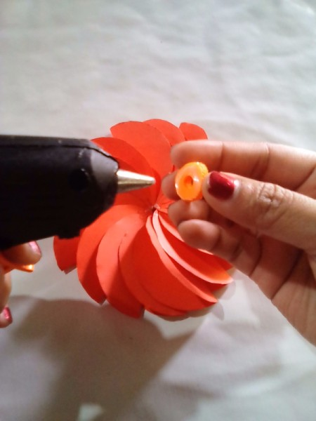 Making Folded Circle Paper Flowers - use hot glue to attach the button to the center of the flower