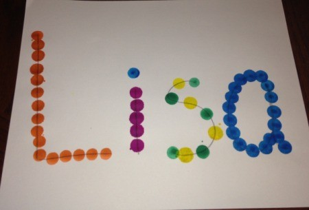 "A piece of paper with the name ""Lisa"" marked in dots with colored bingo markers."