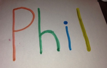 "A piece of paper with the name ""Phil"" written with colored bingo markers."