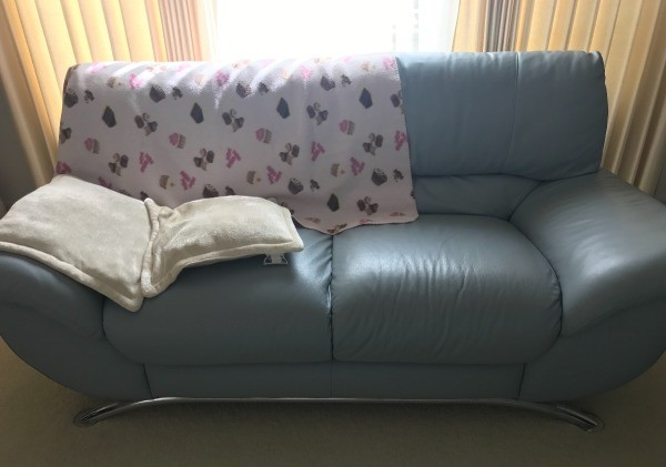 a leather couch with a blanket protecting from sun damage