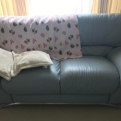 A leather couch with a blanket protecting from sun damage.