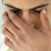 A man touching his eye lid.