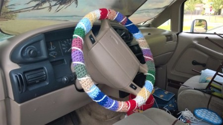 The attached multicolored crocheted steering wheel cover.