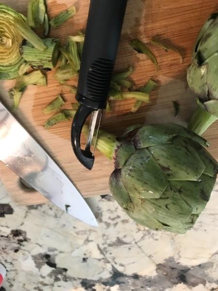 Peeling the stem of an artichoke.