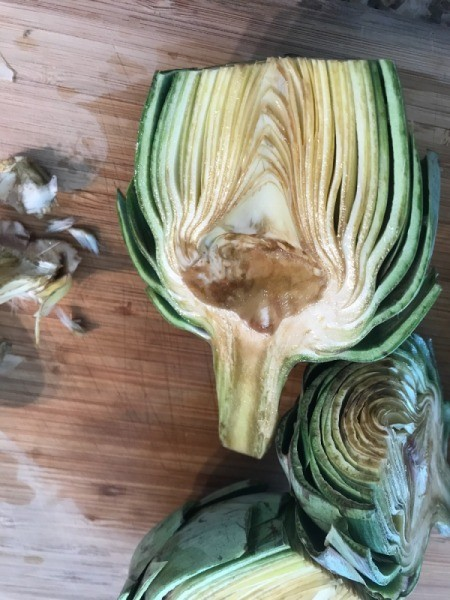 Remove the inner part of the artichoke before grilling.