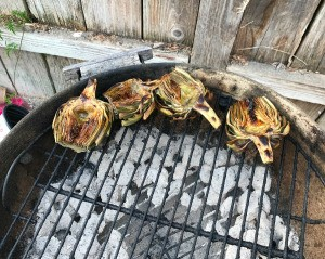 Artichoke halves on the outside edge of a round charcoal grill.